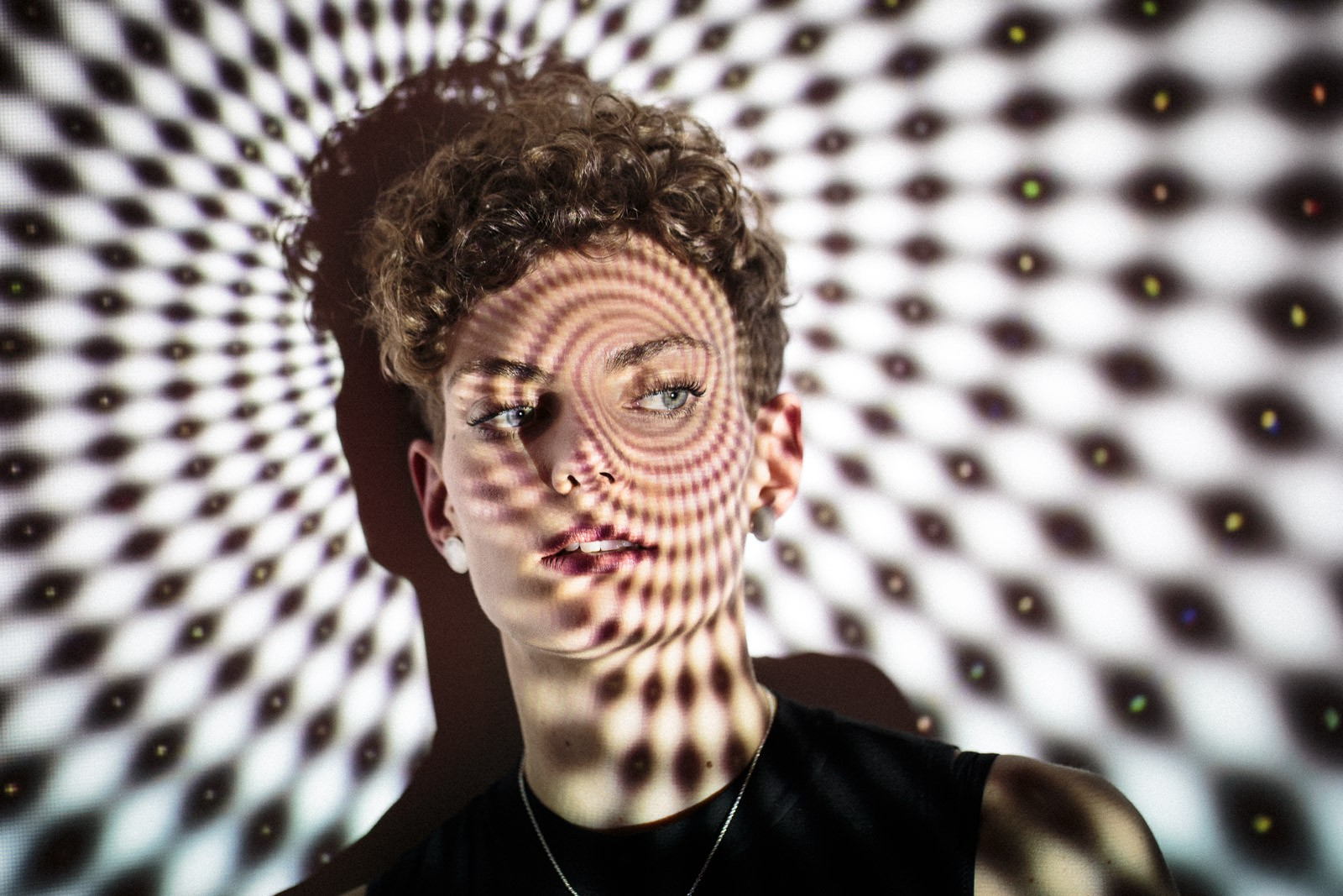 portrait of young woman with short curly hair with projected image of art