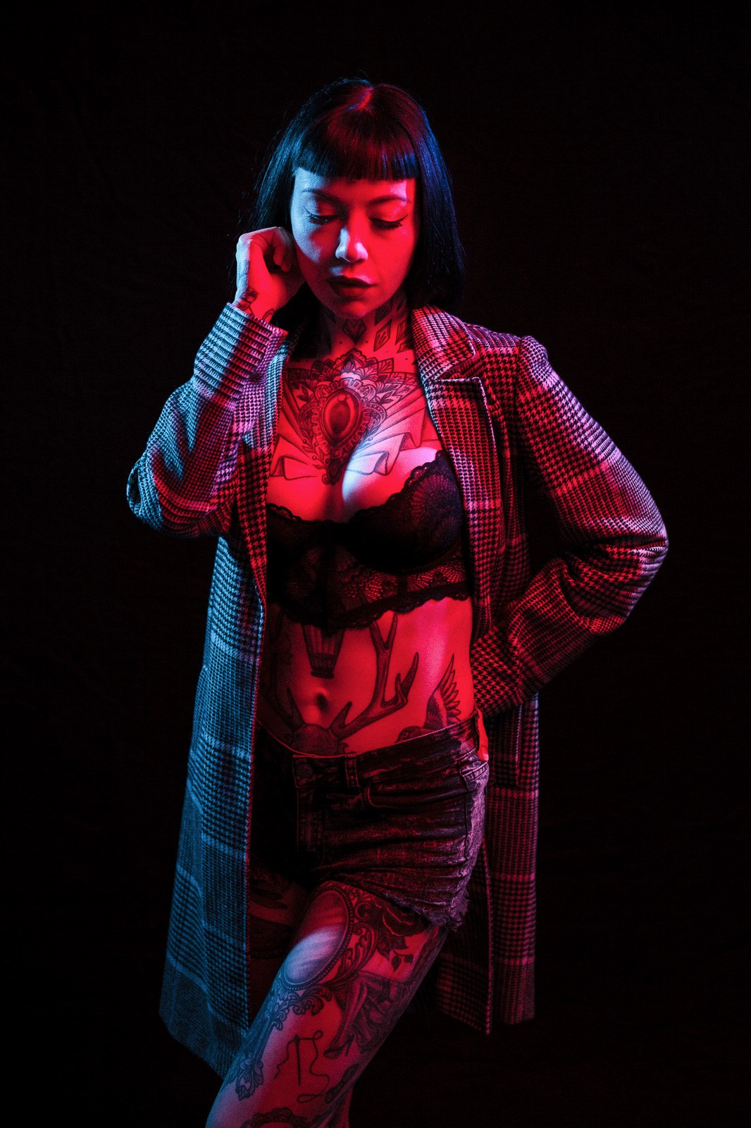 tattooed girl posing with overcoat in blue and red light studio light
