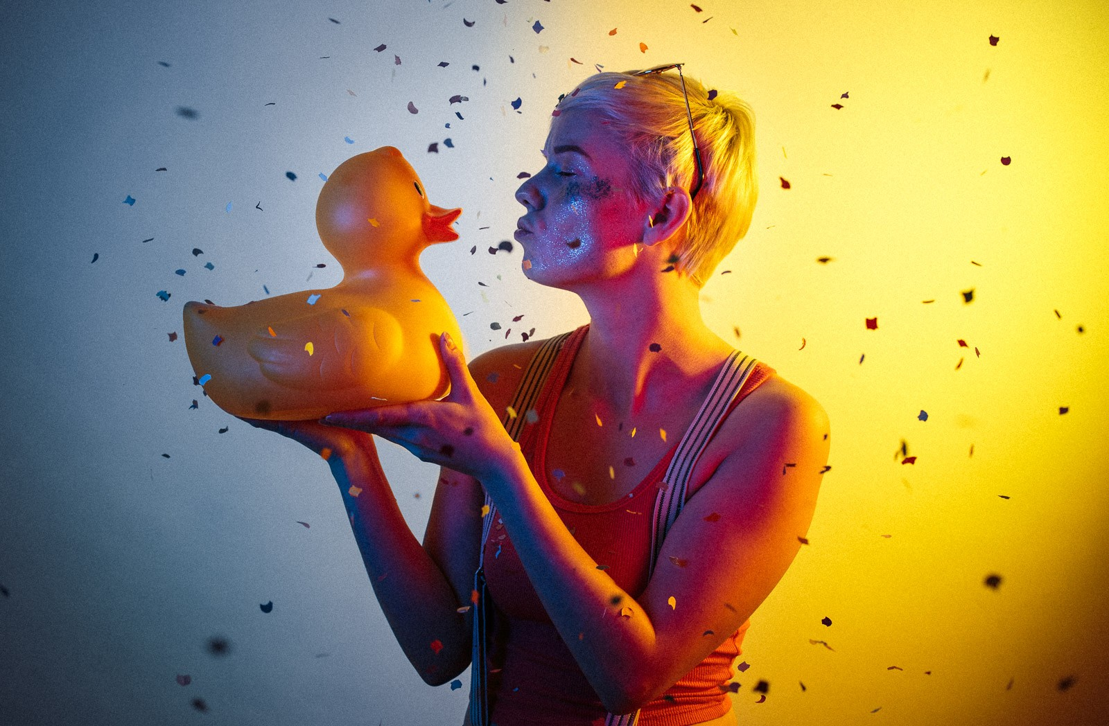 portrait of young woman with short hair wearing sunglasses and holding rubber duck with yellow and blue studio light