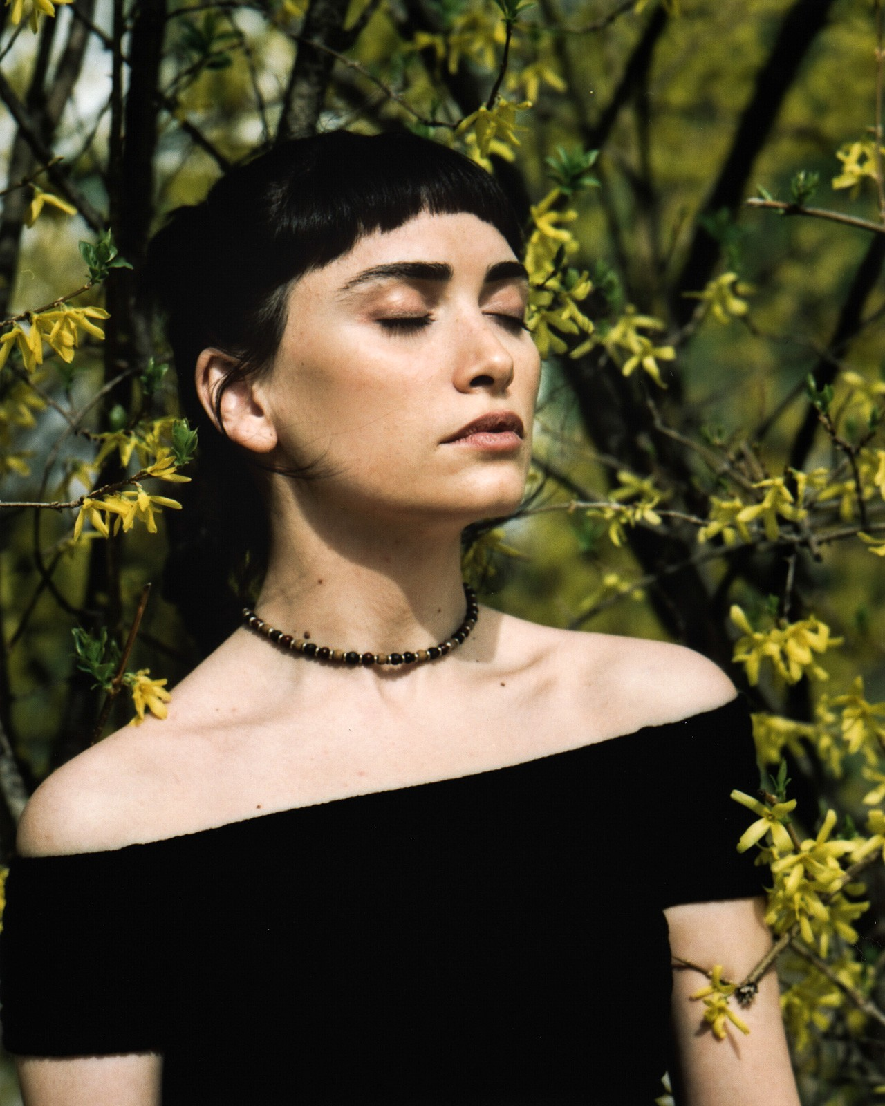 young woman with black top in bush of flowers