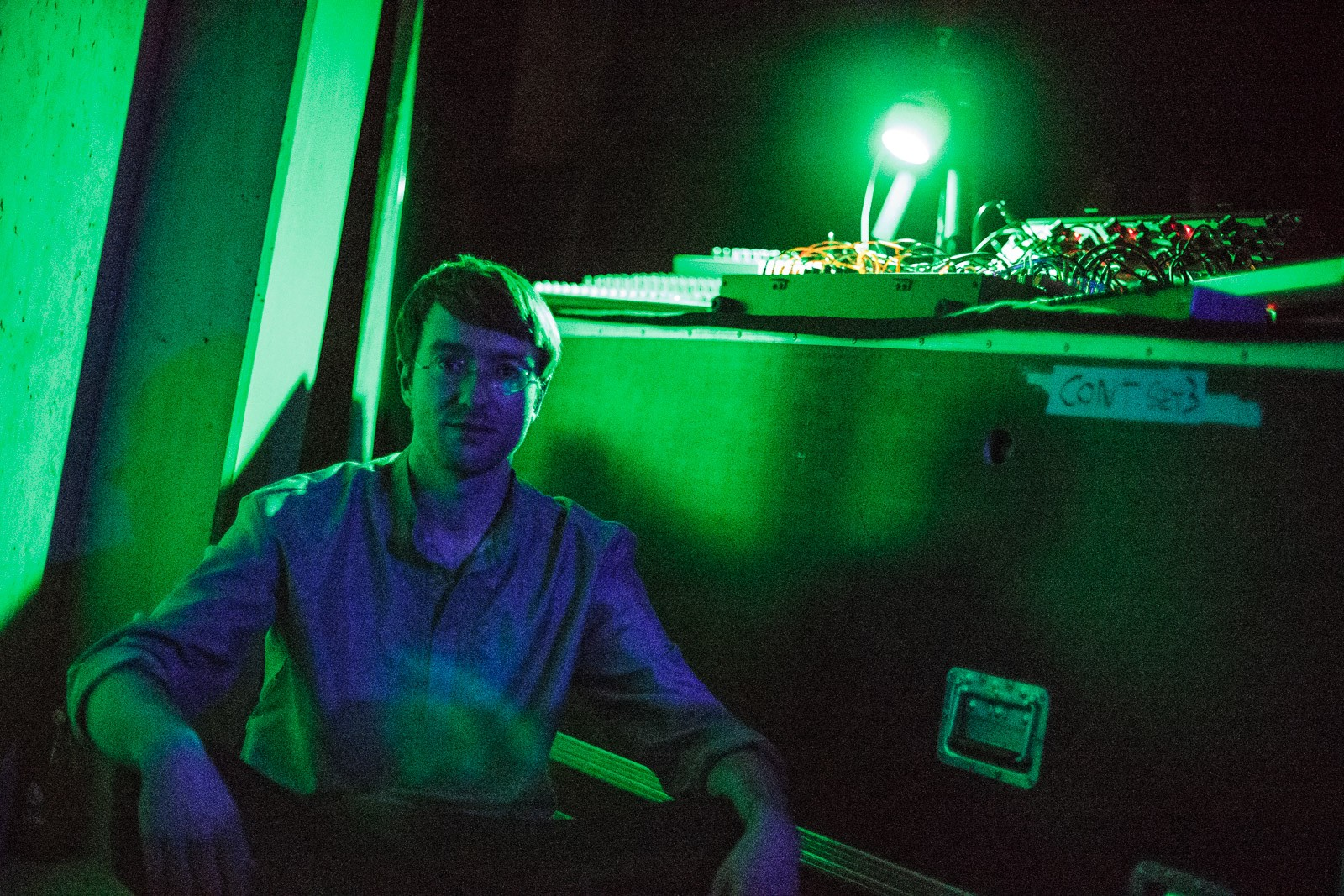 portrait of electronic musician in green and blue light