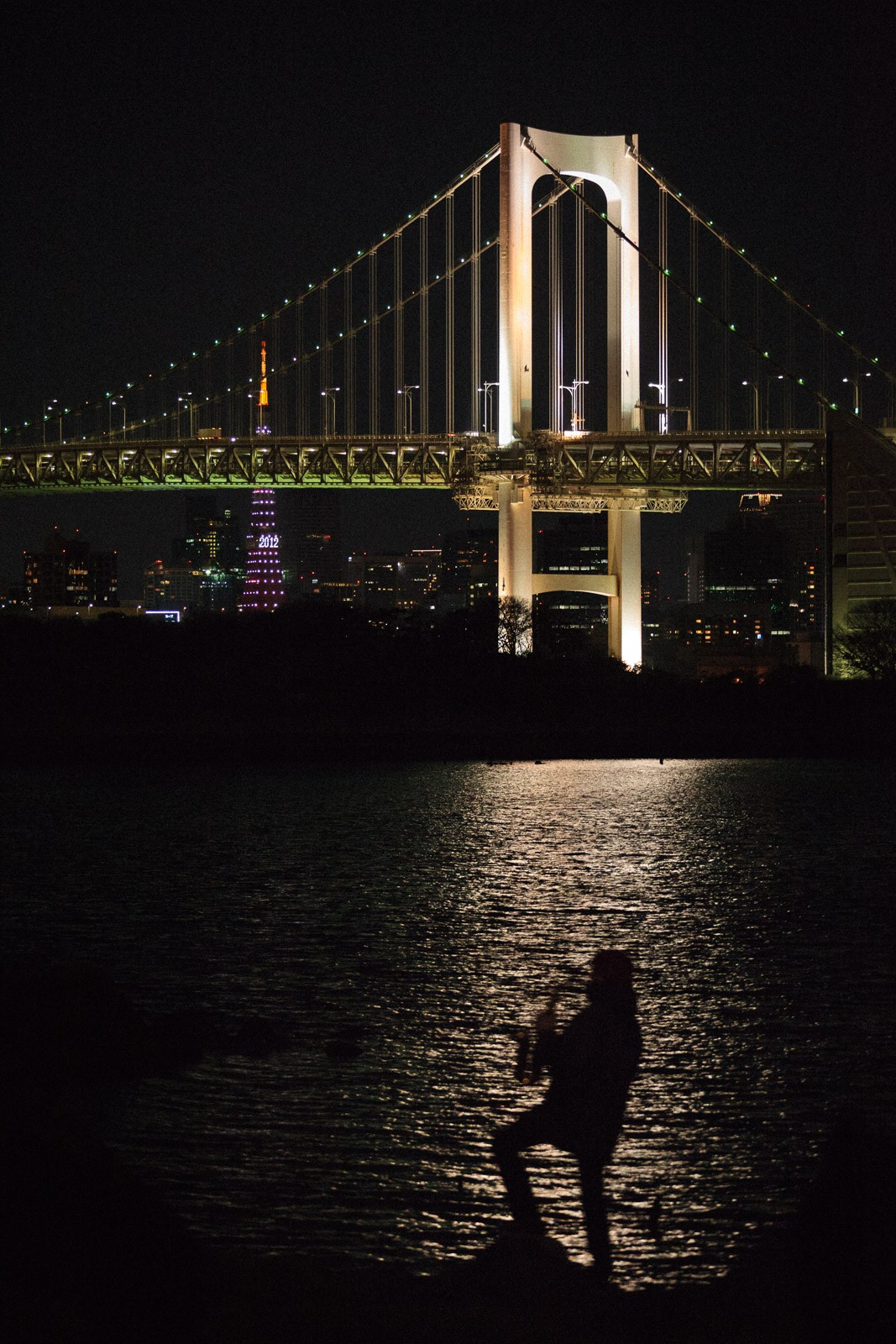 saxophone player at night in tokyo in front of rainbow bridge