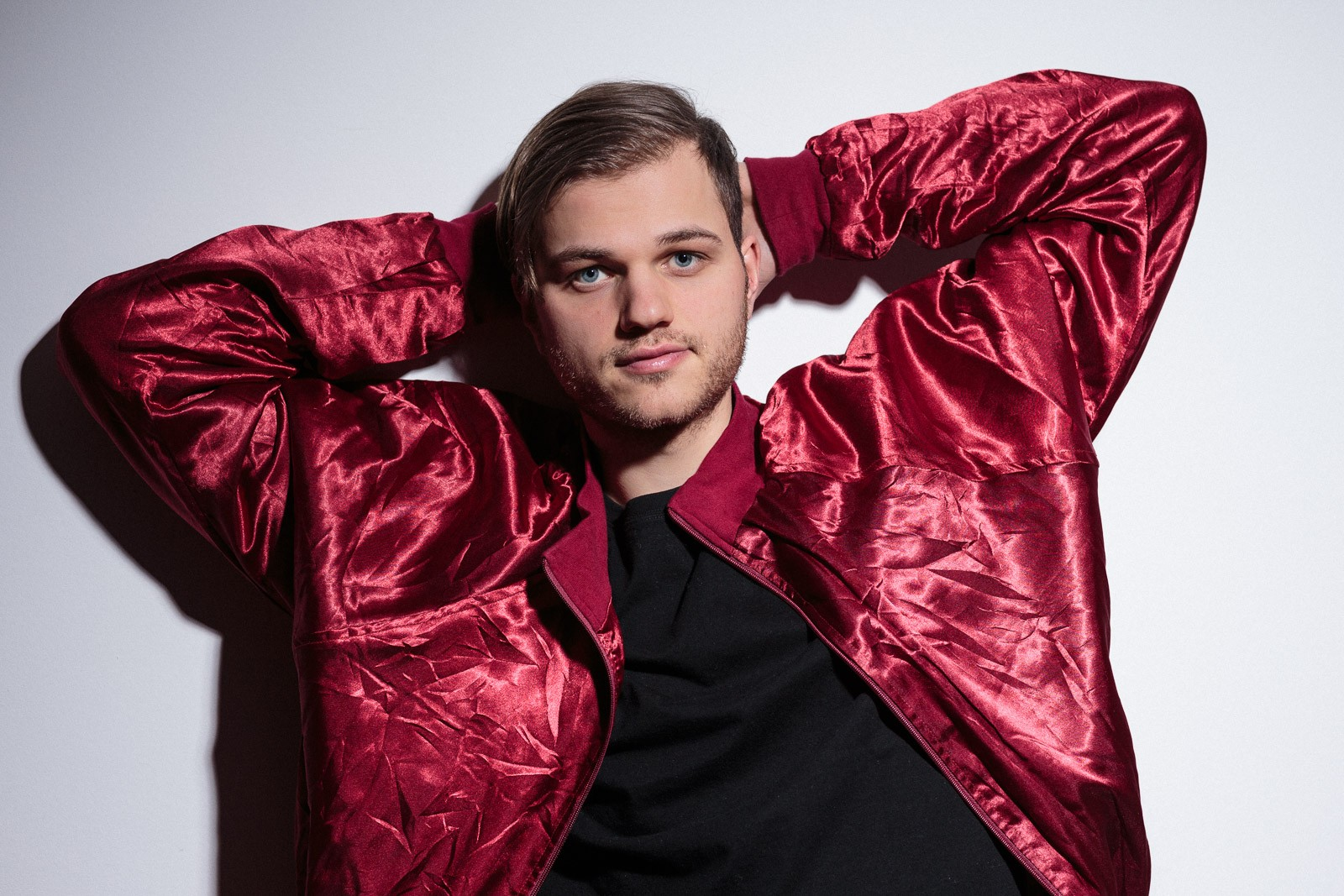 young man wearing shiny red bomber jacket