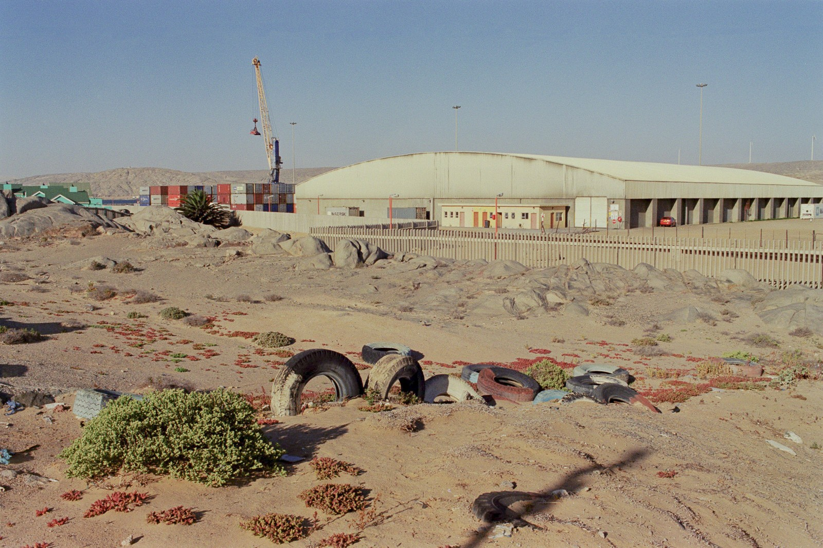 wasteland scene in lüderitz namibia of old tyres in front of industry